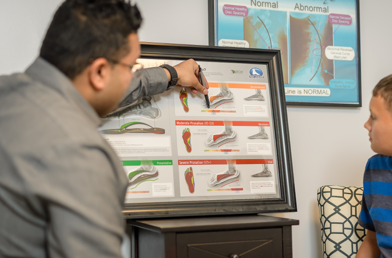 Professional at Monahan Chiropractic Medical Clinics in St. Augustine, Florida explaining the bones in the foot to a patient